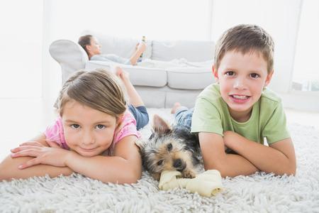 mujer con perro: Hermanos que mienten en la alfombra con yorkshire terrier sonriendo a la c�mara en casa en la sala de estar Foto de archivo