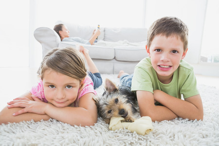 Siblings lying on rug with yorkshire terrier smiling at camera at home in the living room photo