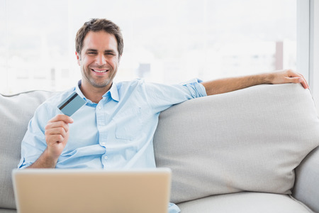 Happy man using laptop sitting on sofa shopping online at home in the living room photo