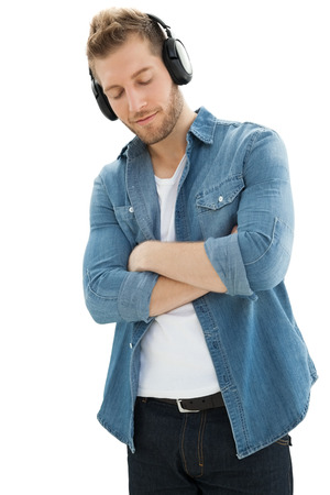 Handsome of a young man enjoying music over white background photo