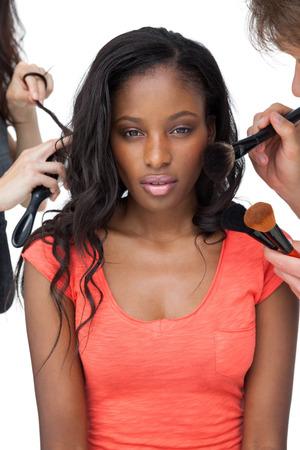 modelos hombres: Asistentes que aplican maquillaje a un modelo femenino sobre fondo blanco