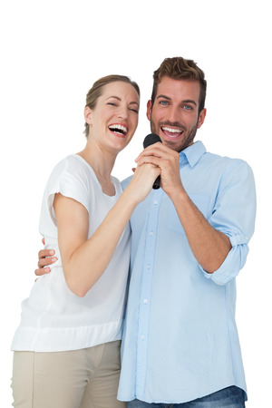 Portrait of a cheerful couple singing into microphone over white background photo