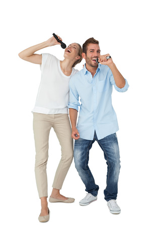 Full length of a cheerful couple singing into microphones over white background photo