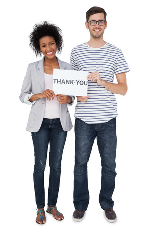 thank you note: Full length portrait of a smiling couple holding a thank you note over white background
