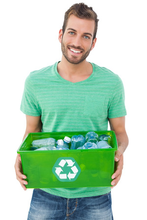 Portrait of a smiling young man carrying recycle container over white background