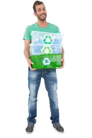 Portrait of a smiling young man carrying recycle containers over white background Stock Photo