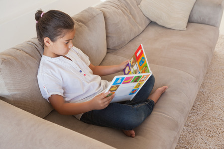 storybook: Side view of a relaxed girl reading storybook on sofa in the living room at home