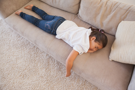 High angle view of a young girl sleeping on sofa in the living room at home photo