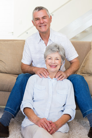 Man giving his relaxed senior wife a shoulder rub smiling at camera at home in living room photo