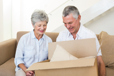 Smiling senior couple moving into new home and unpacking box photo