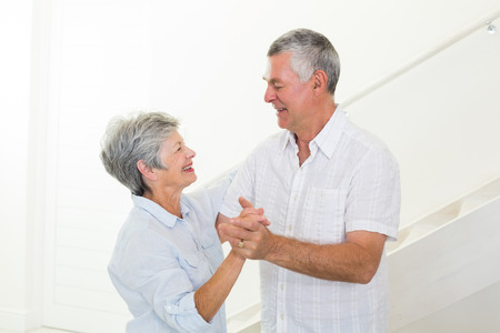Cheerful senior couple dancing together at home in living room photo