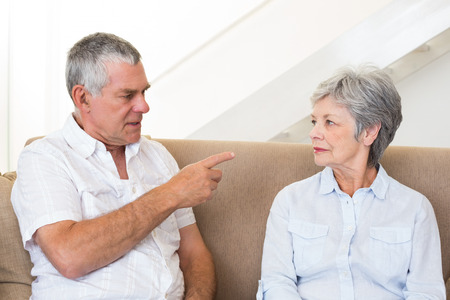 Senior couple sitting on couch having an argument at home in living room photo
