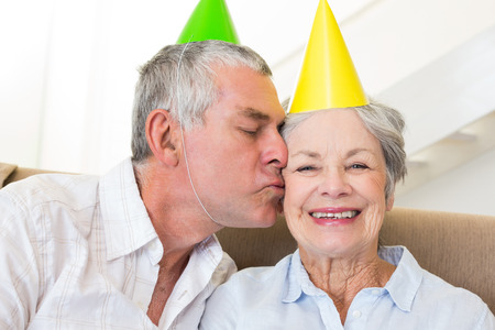 Senior couple sitting on couch wearing party hats at home in living room photo