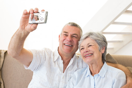 Senior couple sitting on couch taking a selfie at home in living room photo