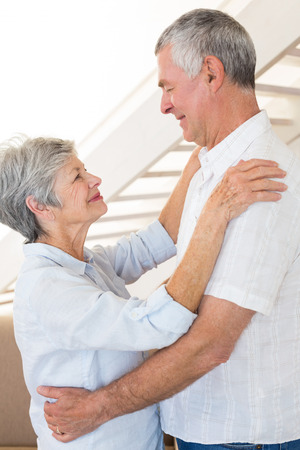 Affectionate senior couple dancing together at home in living room photo