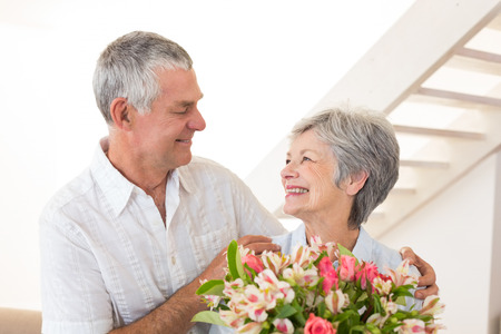 Senior couple smiling at each other holding bouquet of flowers at home in living room
