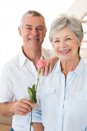 Senior man offering a rose to his partner smiling at camera at home in living room photo