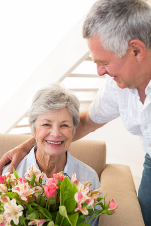 Senior man giving his partner a bouquet of flowers smiling at camera at home in living room photo