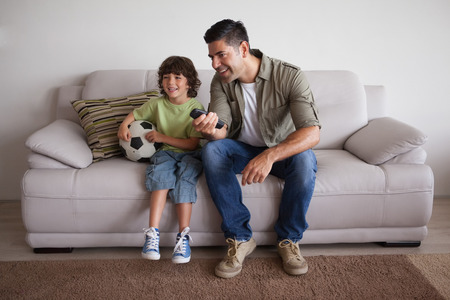 Full length of a happy father and son with football watching tv in the living room at home photo