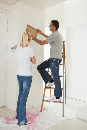 Full length rear view of a couple decorating their new house photo