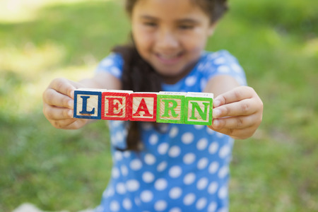 Close-up portrait of a happy young girl holding block alphabets as 'learn' at the park photo