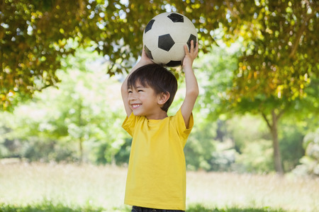 Happy cute little boy holding up football at the park photo