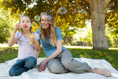 Full length of a smiling mother with her daughter blowing soap bubbles at the park photo