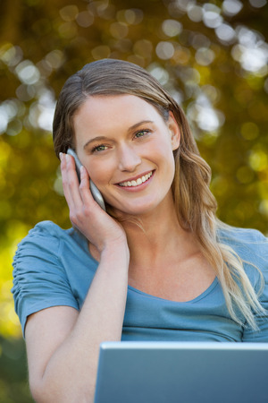 Close-up of a relaxed young woman using laptop and mobile phone at the park photo