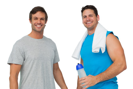 Portrait of two fit young men with water bottle and towel standing over white background photo