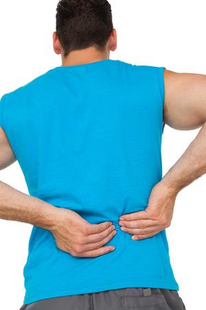 spinal manipulation: Vista posteriore di un giovane uomo in abiti sportivi che soffrono di mal di schiena su sfondo bianco