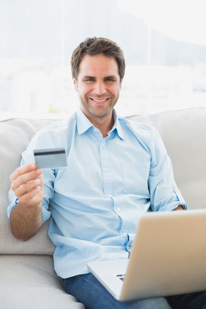 Smiling man using laptop sitting on sofa shopping online at home in the living room photo