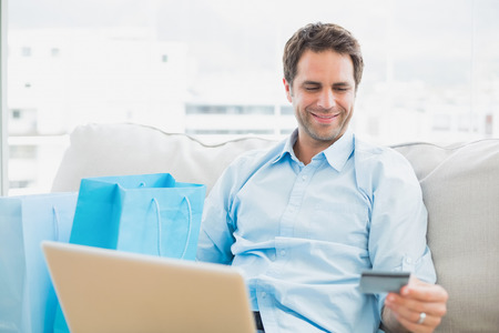 Handsome man using laptop sitting on sofa shopping online at home in the living room photo