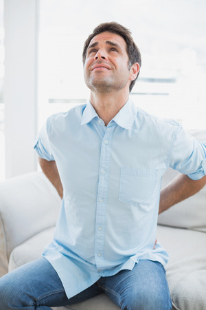 Handsome man sitting on sofa stretching painful back at home in the living room photo