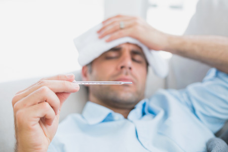 caucasian fever: Sick man lying on sofa checking his temperature at home in the living room