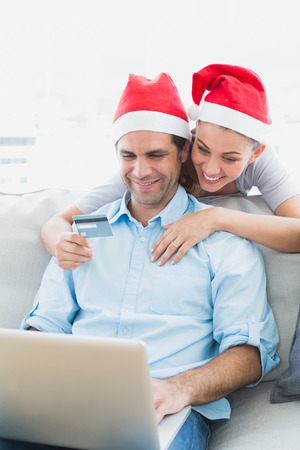 Cute couple in santa hats shopping online with laptop at home in the living room photo
