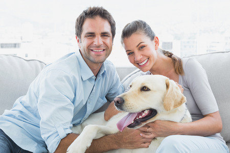 Smiling couple petting their yellow labrador on the couch at home in the living room photo