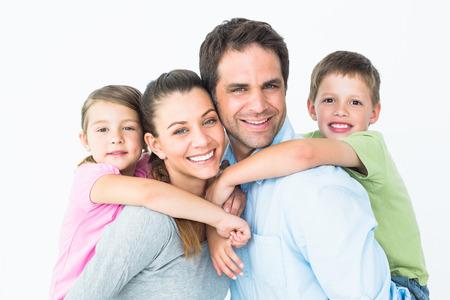 famille: La jeune famille heureuse regardant la cam�ra ensemble sur fond blanc