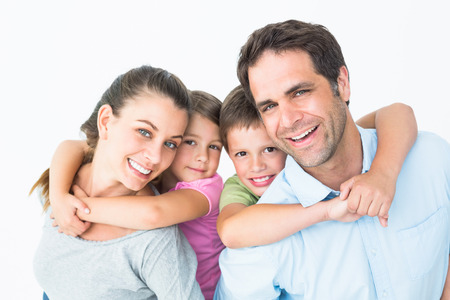 Smiling young family looking at camera together on white background