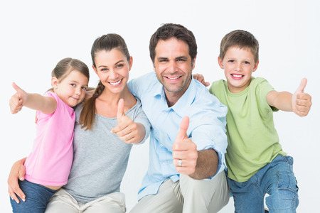 Cute family smiling at camera together showing thumbs up on white background photo