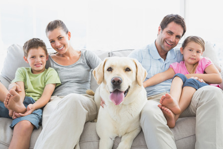 homely: Happy family sitting on couch with their pet labrador at home in the living room
