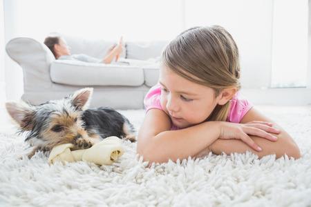 deitado: Menina deitada no tapete com yorkshire terrier em casa na sala de estar