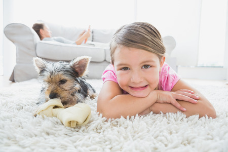 Little girl lying on rug with yorkshire terrier smiling at camera at home in the living room photo
