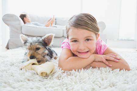 Niña que miente en la alfombra con yorkshire terrier sonriendo a la cámara en casa, en la sala de estar