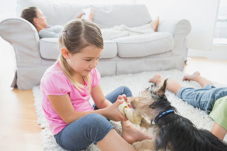 Siblings lying on rug with their yorkshire terrier at home in the living room photo