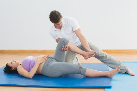 Masseur moving pregnant womans leg on blue mat in a fitness studio photo