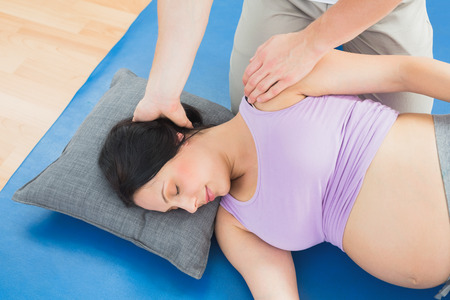 adult pregnant: Masseur moving pregnant womans neck and shoulder in a fitness studio