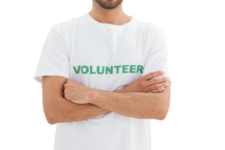 altruism: Primer plano a mediados sección de un voluntario varón joven con las manos cruzadas sobre fondo blanco