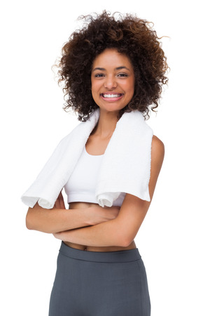 Portrait of a fit young woman with towel standing over white background photo