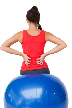 back sprains: Rear view of a fit young woman sitting on exercise ball over white background
