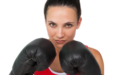 Close-up portrait of a determined female boxer focused on her training over white background photo